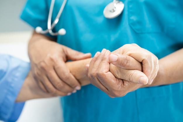 Docteur tenant des mains touchantes patiente asiatique âgée avec amour