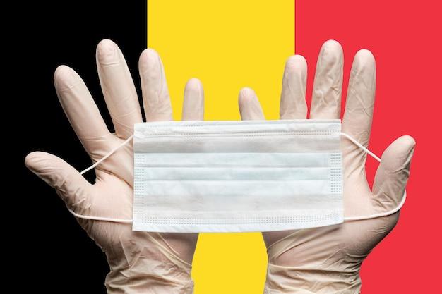 Docteur tenant un masque médical à deux mains dans des gants blancs sur fond de drapeau de la belgique concept