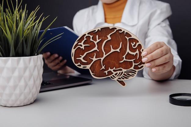 Docteur tenant le modèle en bois du cerveau. concept de soins de santé et de diagnostic précoce.