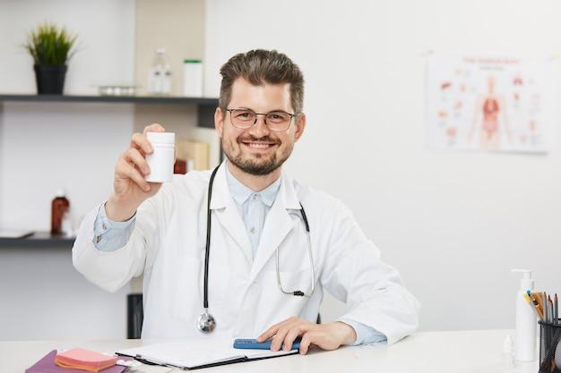 Docteur tenant un pot de comprimés et souriant, thérapeute masculin barbu en robe médicale blanche et lunettes assis dans une armoire médicale avec stéthoscope et montrant des pilules