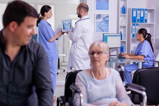 Docteur tenant une radiographie du patient expliquant le diagnostic à l'infirmière dans la zone d'attente