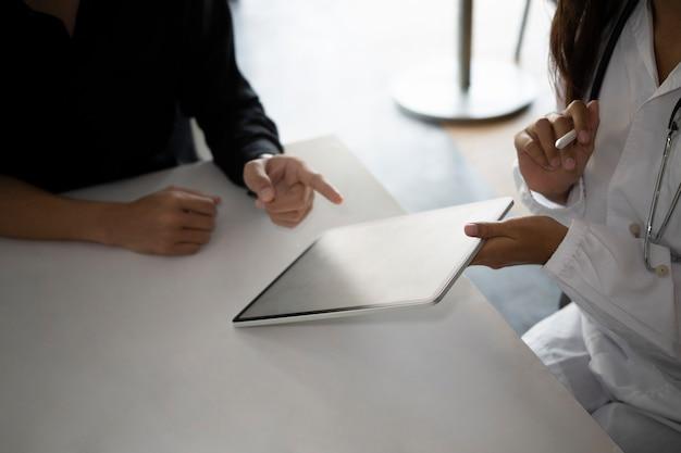 Docteur tenant une tablette et expliquant le plan de traitement pour le patient.