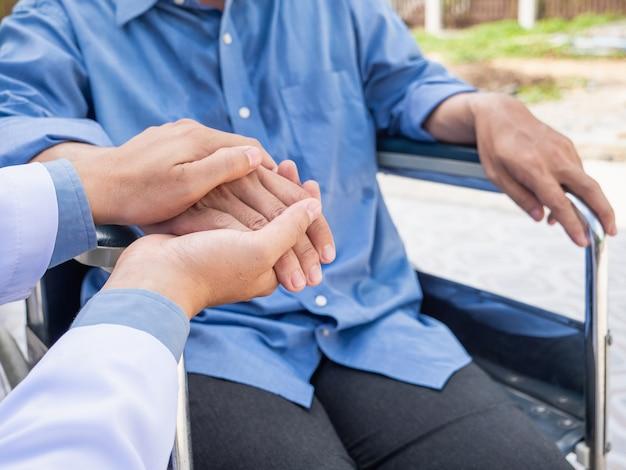 Docteur tenir le patient de la main sur un fauteuil roulant.