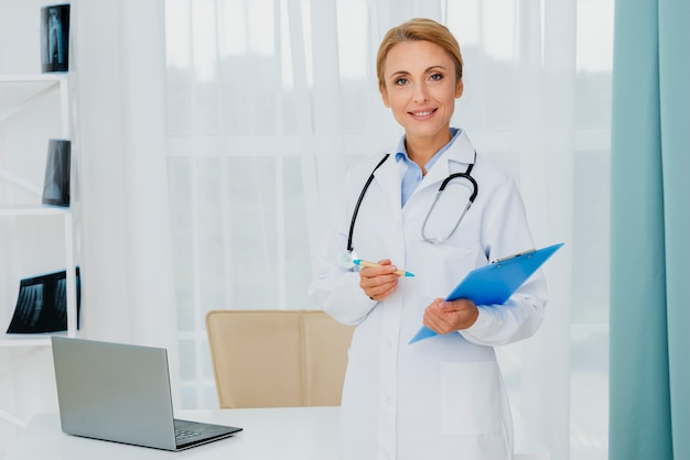 Docteur, tenue, presse-papiers, regarder caméra