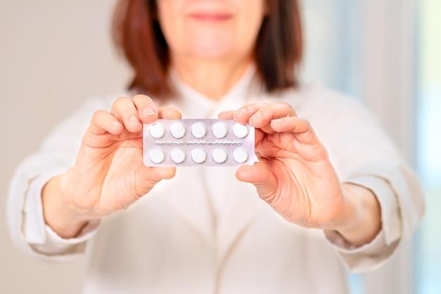 Le docteur tient des pilules dans ses mains.