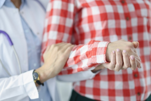 Le docteur tient sympathiquement le patient malade à la main en aidant le concept des patients en phase terminale