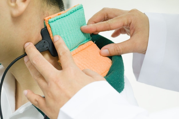 Docteur traiter la douleur avec un stimulateur musculaire.