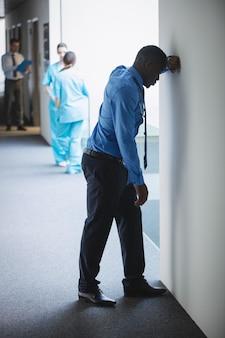 Docteur triste s'appuyant sur le mur