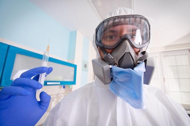 Docteur en uniforme de protection et masque détient la seringue d'injection avec le vaccin.