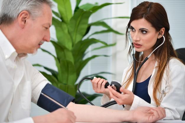Docteur utilisant un stéthoscope et un sphygmomanomètre pour vérifier la pression artérielle