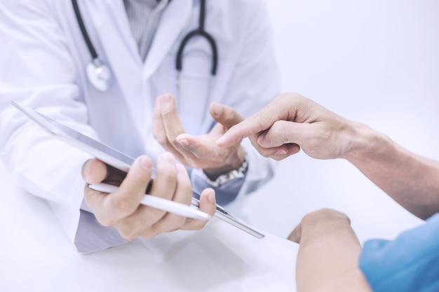 Docteur en utilisant une tablette numérique et poser des questions sur la maladie des patients