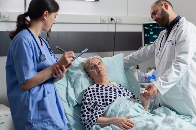 Docteur vérifiant le patient supérieur dans le soin intensif d'hôpital
