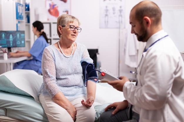 Docteur vérifiant la tension de la femme à l'aide de la pression numérique du bras portable pour vérifier le flux sanguin