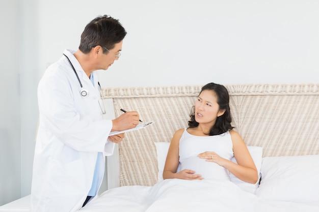 Docteur, visite, femme enceinte, dans chambre à coucher
