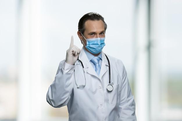 Le docteur vous prévient en pointant le doigt vers le haut. veuillez noter la prescription. debout dans une pièce lumineuse.