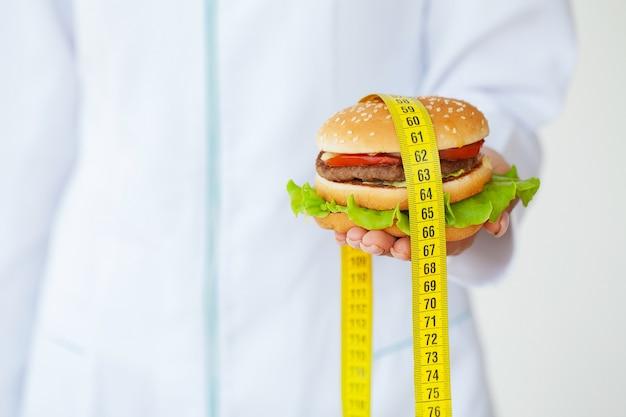 Doctor holding burger gras nocifs avec ruban à mesurer jaune