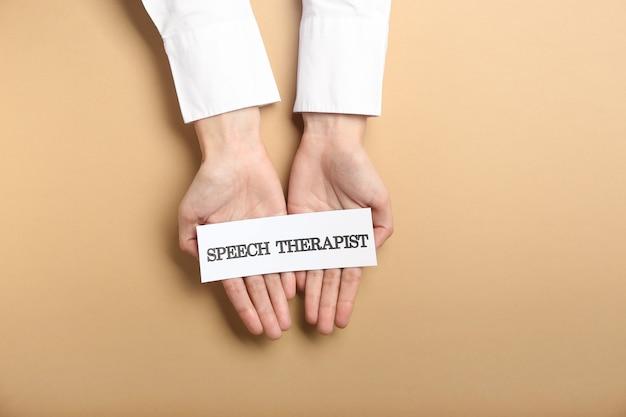 Doctor holding paper avec texte speech therapist sur la surface de couleur