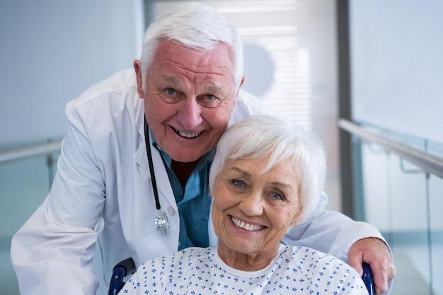 Doctor holding senior patient sur fauteuil roulant dans le passage à l'hôpital