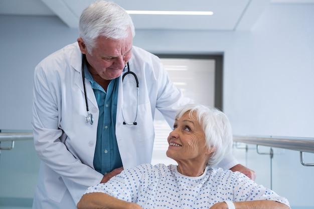Doctor holding senior patient sur fauteuil roulant dans le passage
