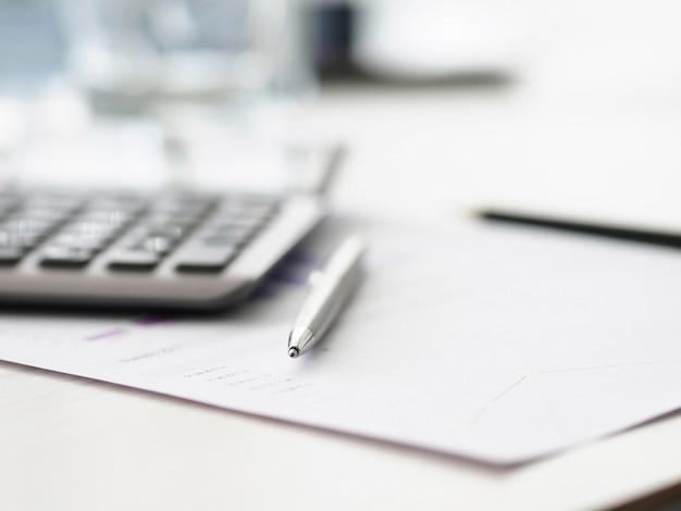 Sur le document de bureau se trouve un stylo argenté et une calculatrice