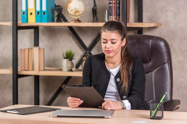 Document de lecture de femme d'affaires brune