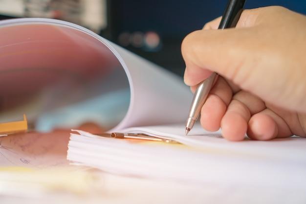 Document de rapport et affaires en cours concept: gestionnaire d'hommes d'affaires vérifiant et signant des documents de rapports avec une calculatrice, un ordinateur portable sur des piles de fichiers dans un bureau moderne.