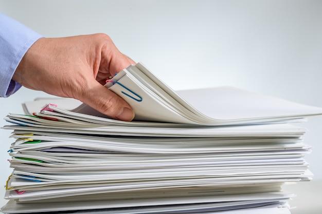 Un document ou un rapport empilé et la main d'un homme d'affaires qui le tient.