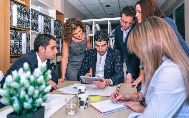 Document à la recherche de travail d'équipe dans une tablette électronique autour du chef d'entreprise au siège de l'entreprise