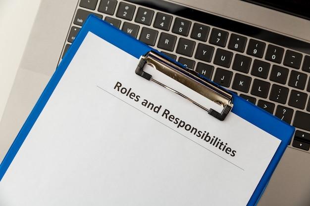 Document sur les rôles et responsabilités dans la tablette à l'ordinateur portable sur la table.