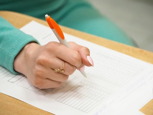 Document de signature de femme, gros plan sur une main féminine tenant un stylo et du papier sur la table. mise au point sélective.
