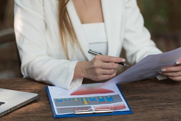Document de vérification et d'analyse de femme d'affaires, graphique ou rapport d'activité sur un bureau.