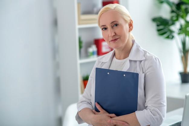 Avec des documents. blonde médecin d'âge moyen tenant des documents et à la recherche positive