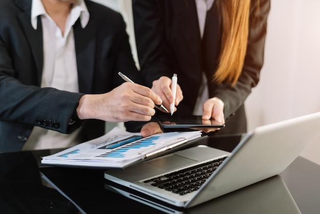 Documents commerciaux sur table de bureau avec téléphone intelligent et calculatrice tablette numérique et entreprise graphique avec diagramme de réseau social et deux collègues discutant des données travaillant au bureau