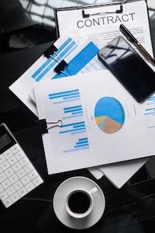 Documents financiers, contrat et tasse à café, vue de dessus, gros plan