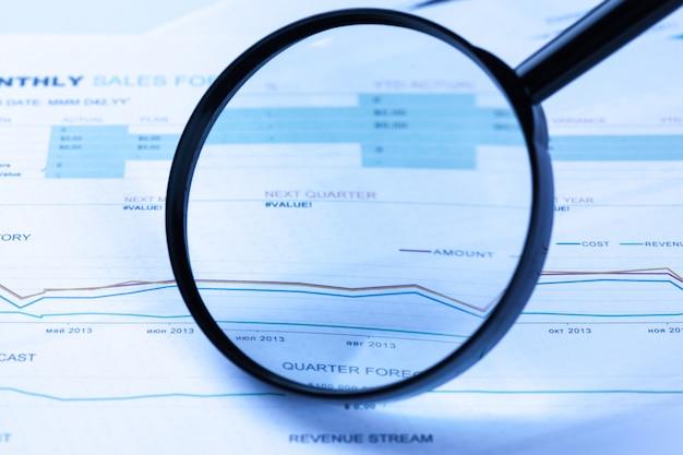Documents financiers avec une loupe dessus