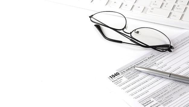 Documents fiscaux pour déclarer des impôts en amérique avec le formulaire irs 1040 et un stylo et un clavier