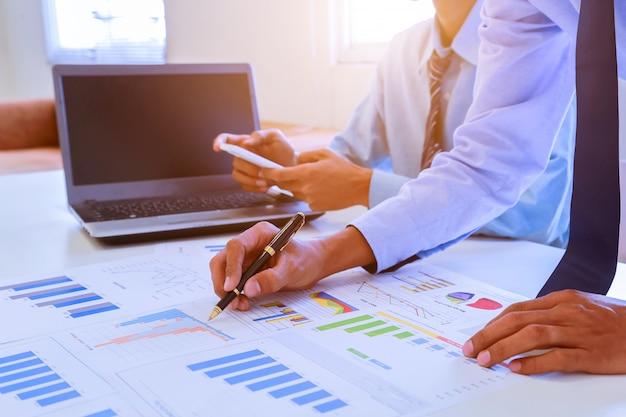 Documents d'homme d'affaires sur la table de bureau avec téléphone intelligent et ordinateur portable et deux collègues