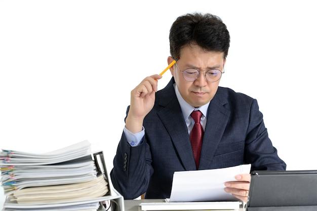 Documents ou rapports empilés avec un homme d'affaires asiatique d'âge moyen.