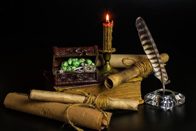 Des documents en rouleaux, une bougie allumée dans un chandelier en bronze, un vieux gros livre, un coffre avec des bijoux sur fond noir.