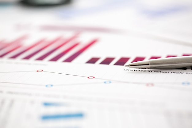Documents de statistiques financières infographie stylo à bille à table de bureau