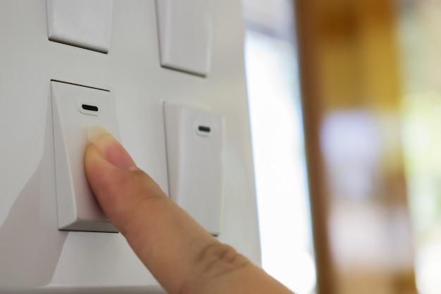 Un doigt allumant le commutateur d'éclairage sur rugueux