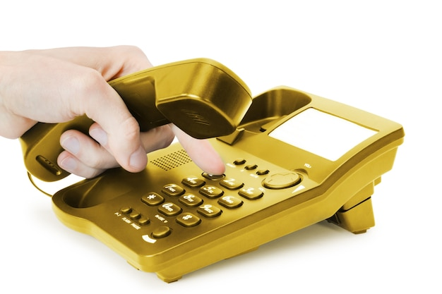 Doigt appuie sur le bouton du téléphone or isolé sur fond blanc.