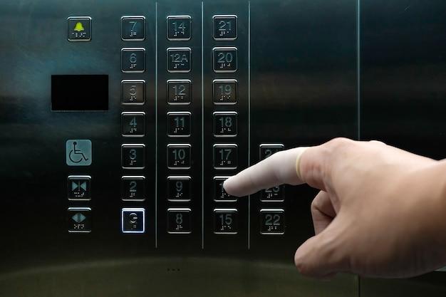 Le doigt appuie sur le bouton de l'élévateur en portant un doigtier pour empêcher le contact direct avec les germes et les bactéries.