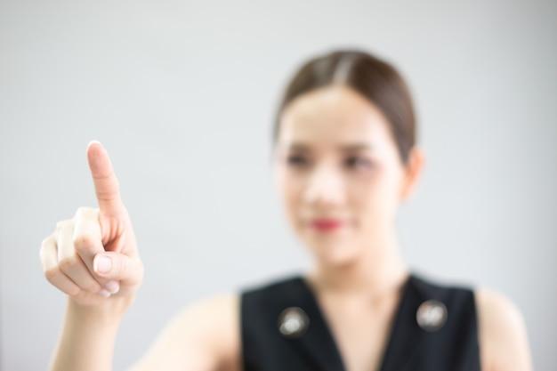 Un doigt appuie sur l'écran tactile. avec un arrière-plan flou.