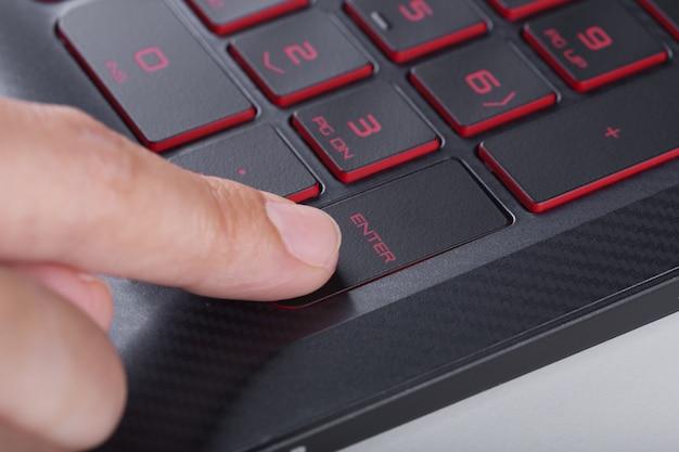 Doigt appuyant sur entrer le bouton sur le clavier d'ordinateur portable