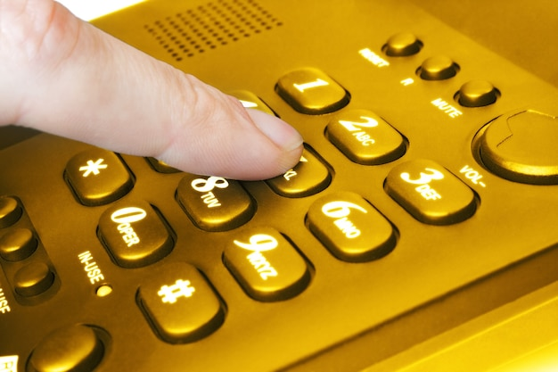 Doigt avec clavier de téléphone doré