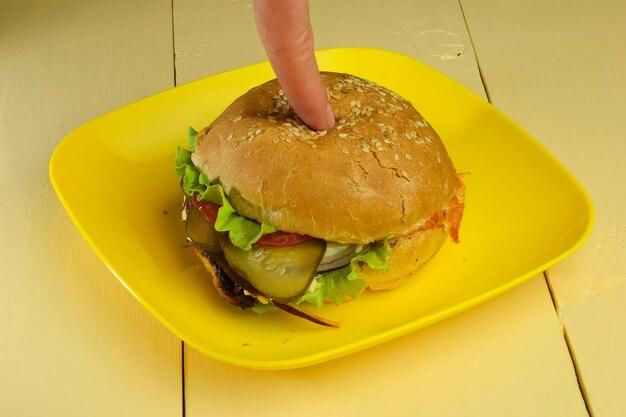Le doigt clique sur un sandwich avec de la viande, du fromage, des tomates, des oignons, des concombres et de la salade sur une assiette sur la table
