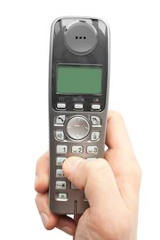 Le doigt compose un numéro de téléphone sur un téléphone sans fil