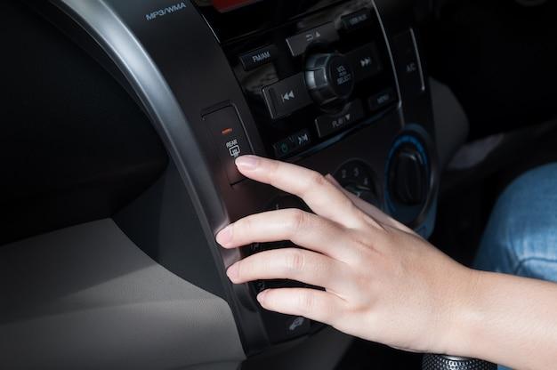 Doigt femme appuyant sur le bouton de dégivrage détail sur le tableau de bord d'une voiture