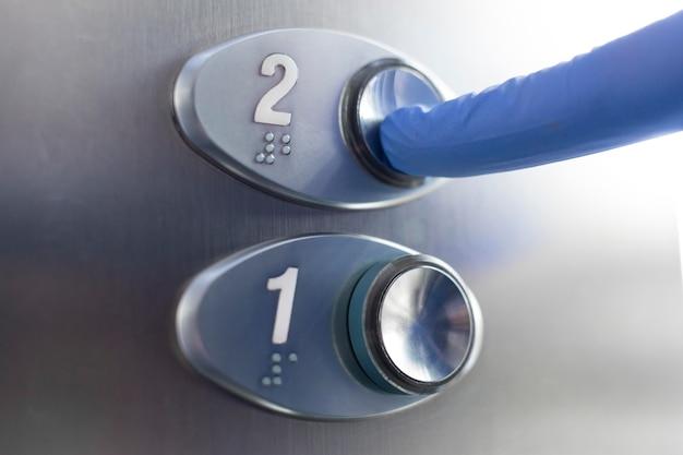 Doigt avec gant touchant le bouton de l'élévateur